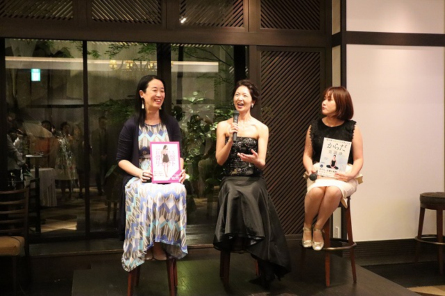 真ん中が主賓、両脇に女性が囲んで話をしているトークショーのステージの写真