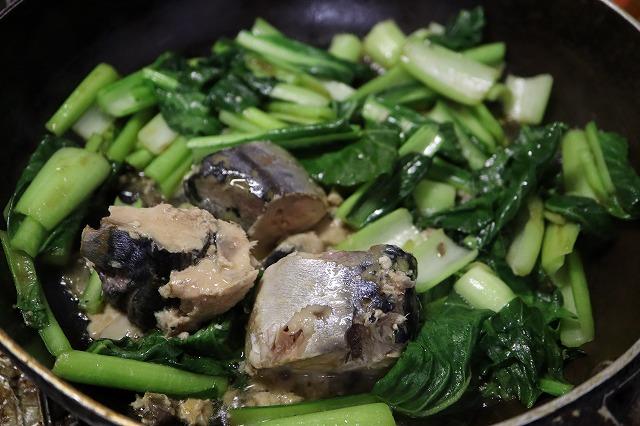 フライパンに小松菜を入れ、サバ缶をいれて料理しているところ