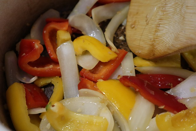 赤パプリカと黄色パプリカを入れて炒めているところ
