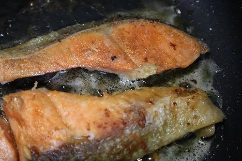 小麦粉をつけた鮭をフライパンで焼いているところ