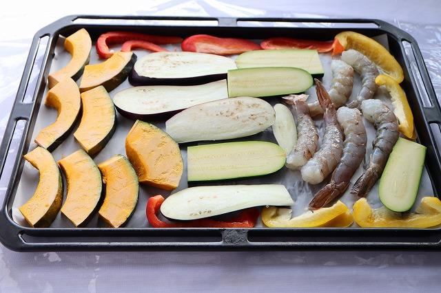 オーブンのトレーに野菜と海老を並べているところ