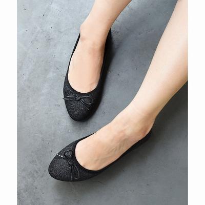 ラメ入りのブラック・パンプスを履いた足