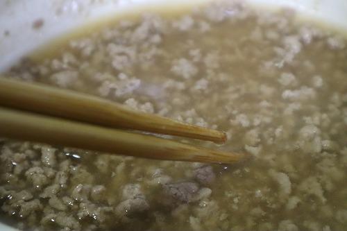挽き肉に調味料を入れて混ぜているところ